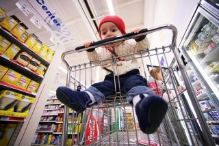 A young child playfully licking a shopping cart handle.